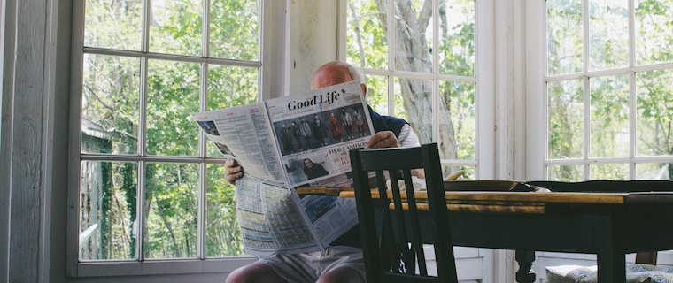 An elderly person reading a newspaper