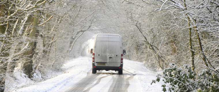 White van driving along country lane